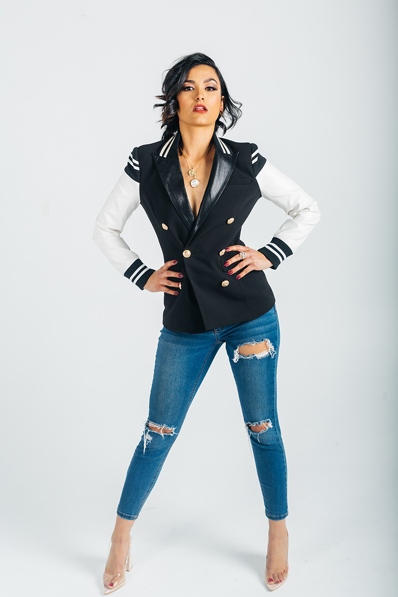 A beautiful young brunette model poses for a RAW Photographic Studio photography session in Denver Colorado wearing a black and white jacket and jeans
