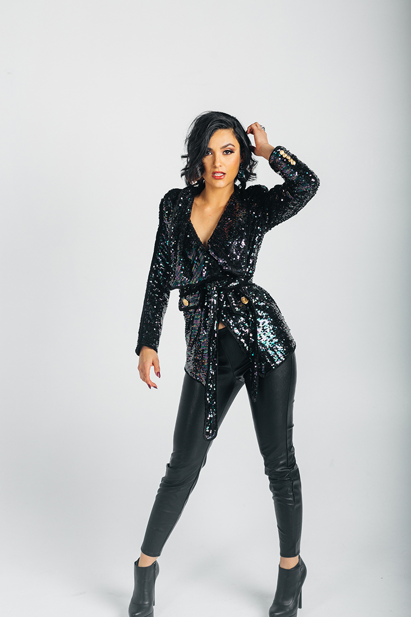 A beautiful young brunette model poses for a RAW Photographic Studio photography session in Denver Colorado wearing a a black sequin top and black pants