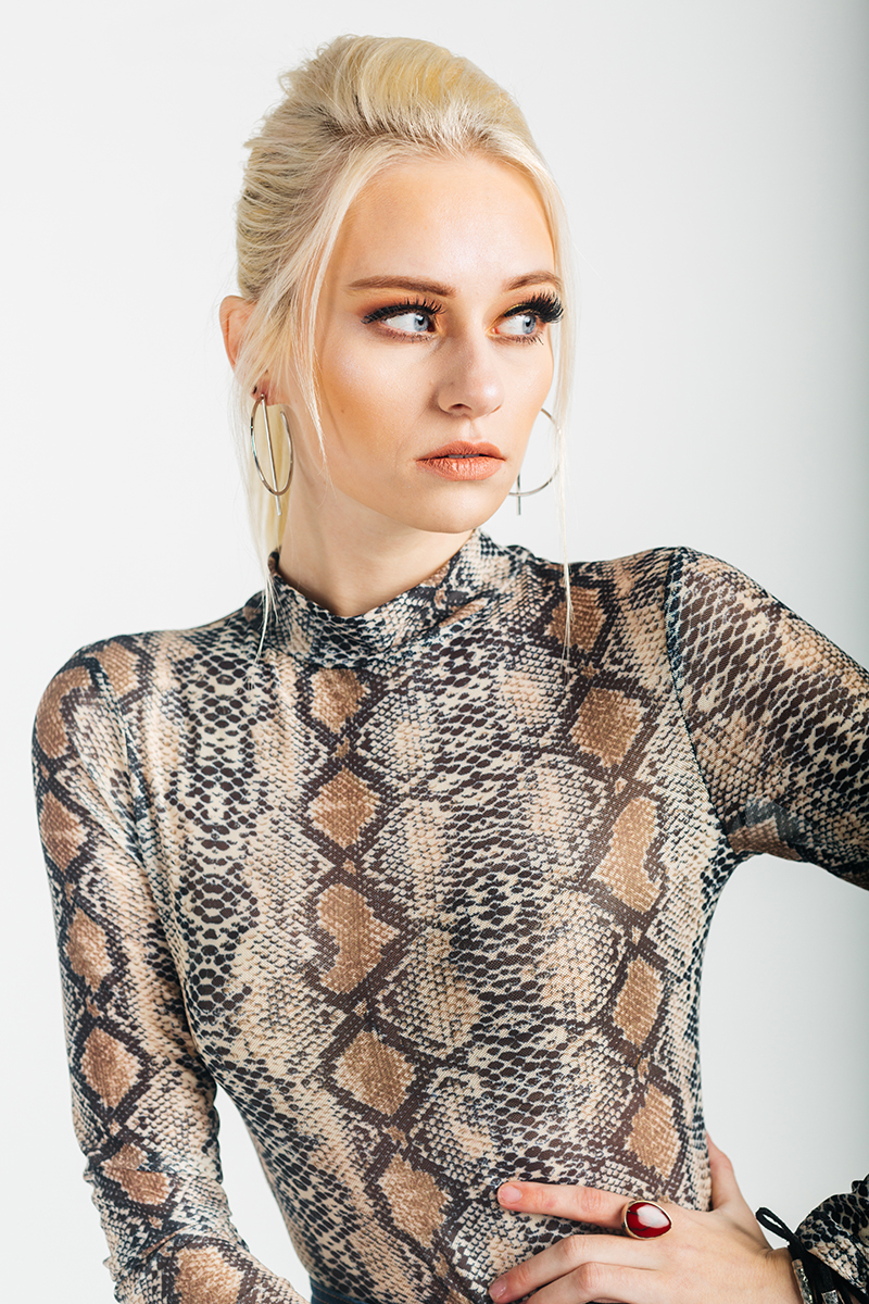 A beautiful young blonde model poses for a RAW Photographic Studio photography session in Denver Colorado wearing a snake skin top and a buckle jean skirt