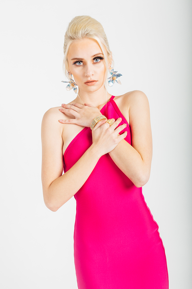 A beautiful young blonde model poses for a RAW Photographic Studio photography session in Denver Colorado wearing a pink dress