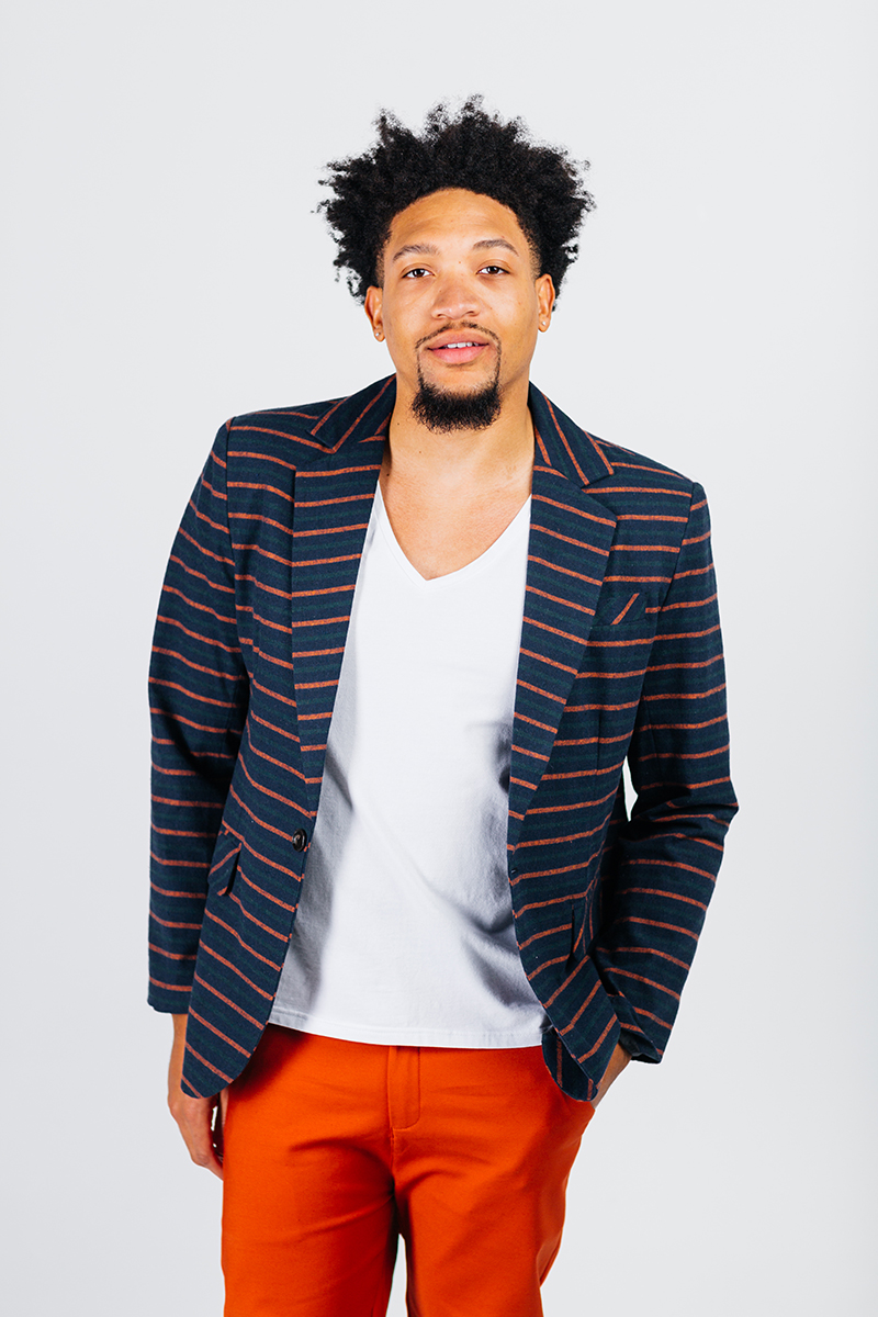 A handsome young brown haired male model poses for a RAW Photographic Studio photography session in Denver Colorado wearing a blue and purple pinstripe jacket, a white v-neck and red pants