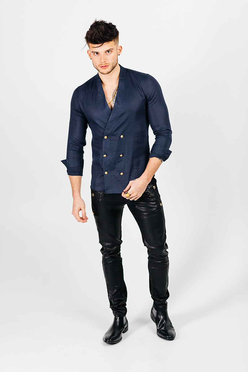 A handsome young brown haired male model poses for a RAW Photographic Studio photography session in Denver Colorado wearing a blue button up shirt and black leather pants