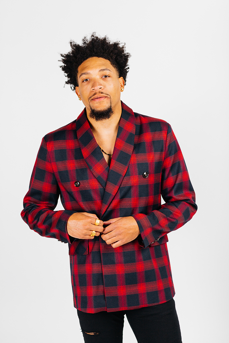 A handsome young brown haired male model poses for a RAW Photographic Studio photography session in Denver Colorado wearing a red and black plaid jacket with black pants