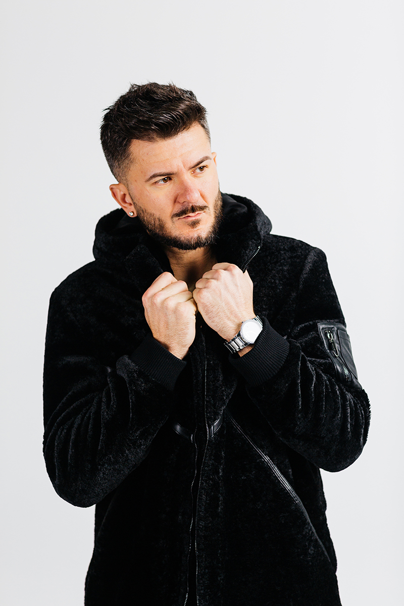 A handsome young brown haired male model poses for a RAW Photographic Studio photography session in Denver Colorado wearing a black jacket