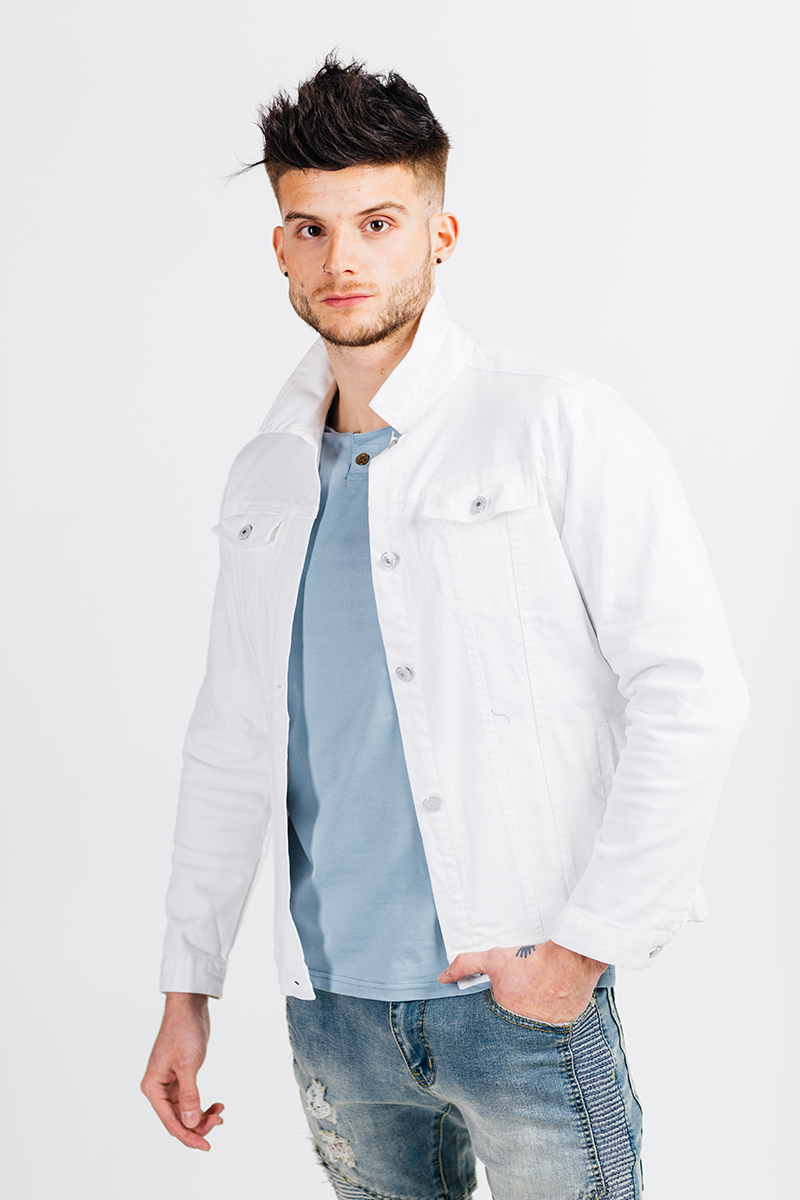 A handsome young brown haired male model poses for a RAW Photographic Studio photography session in Denver Colorado wearing a blue shirt, white jacket and jeans