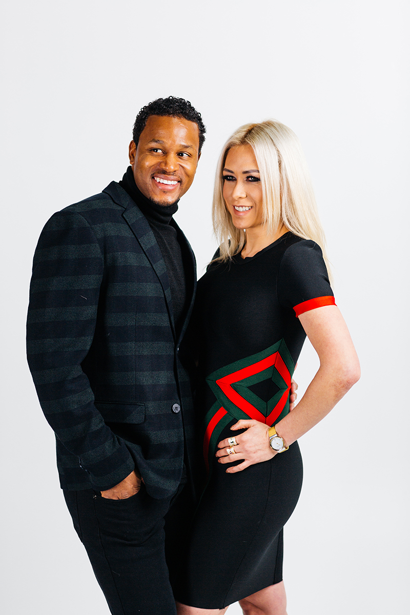 A beautiful young blonde model and a handsome brown haired male pose together for a RAW Photographic Studio photography session in Denver Colorado wearing a black, red and green striped dress and a blue and green jacket with black pants