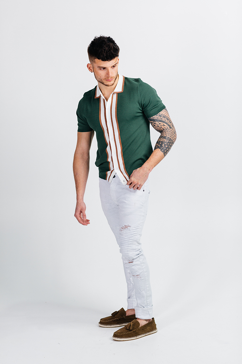 A handsome young brown haired male model poses for a RAW Photographic Studio photography session in Denver Colorado wearing green and white button up shirt with white pants