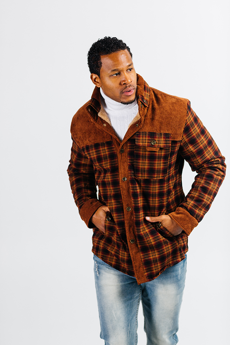 A handsome young brown haired male model poses for a RAW Photographic Studio photography session in Denver Colorado wearing a brown plaid jacket, a white turtleneck and jeans