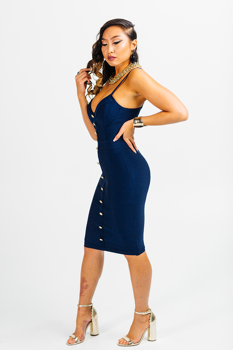 A beautiful young brunette model poses for a RAW Photographic Studio photography session in Denver Colorado wearing a blue dress
