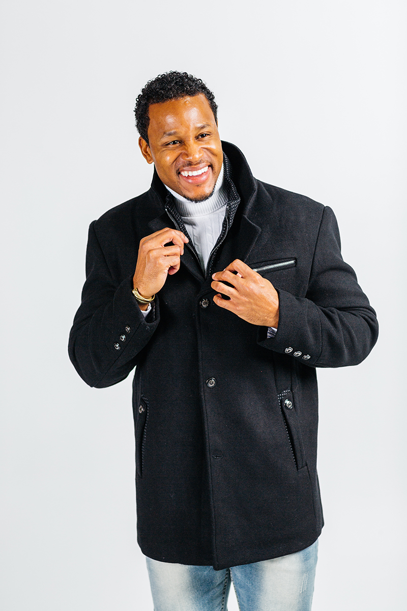 A handsome young brown haired male model poses for a RAW Photographic Studio photography session in Denver Colorado wearing a black jacket, a white turtleneck and jeans