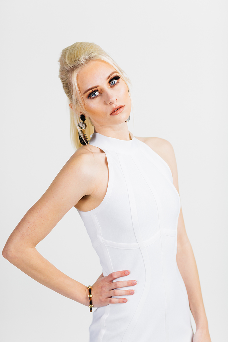 A beautiful young blonde model poses for a RAW Photographic Studio photography session in Denver Colorado wearing a white dress