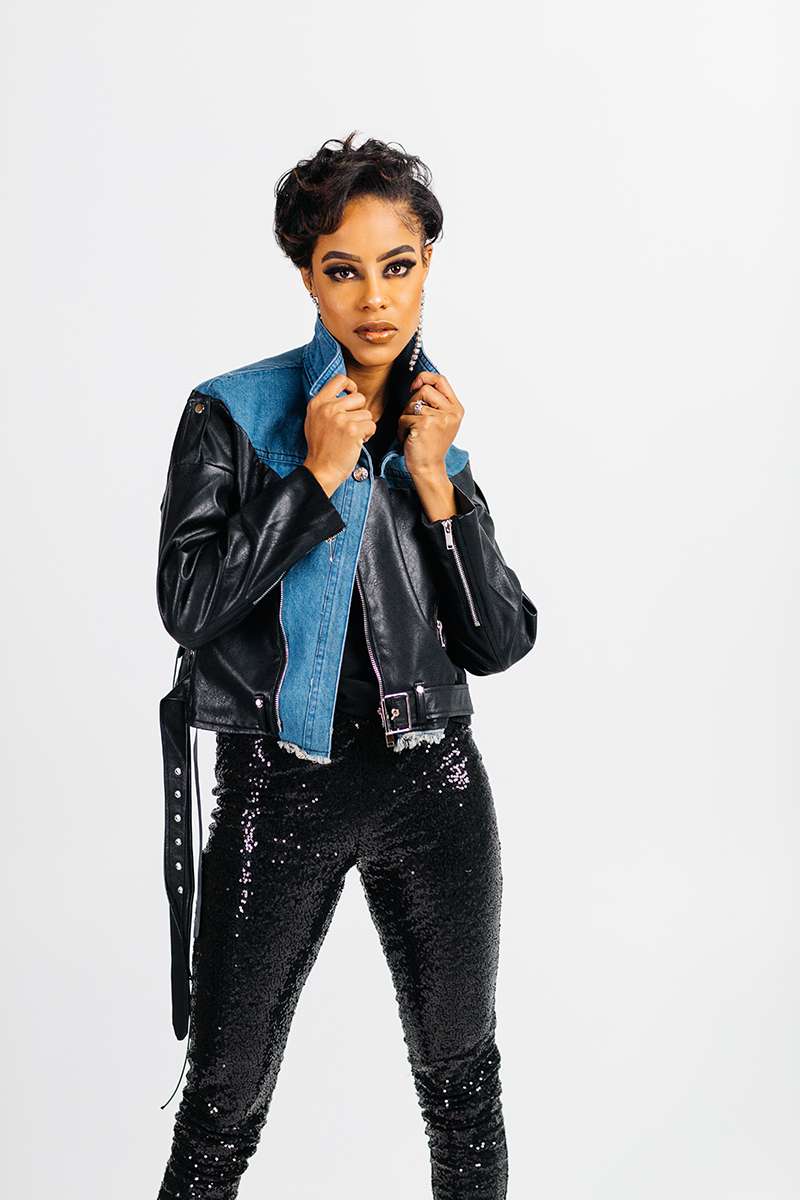 A beautiful young brunette model poses for a RAW Photographic Studio photography session in Denver Colorado wearing black sequin pants and a black leather and jean jacket