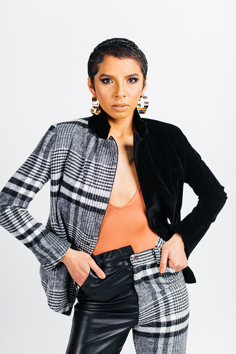 A beautiful young brunette model poses for a RAW Photographic Studio photography session in Denver Colorado wearing an orange shirt and a black and white pinstripe jacket and pant set