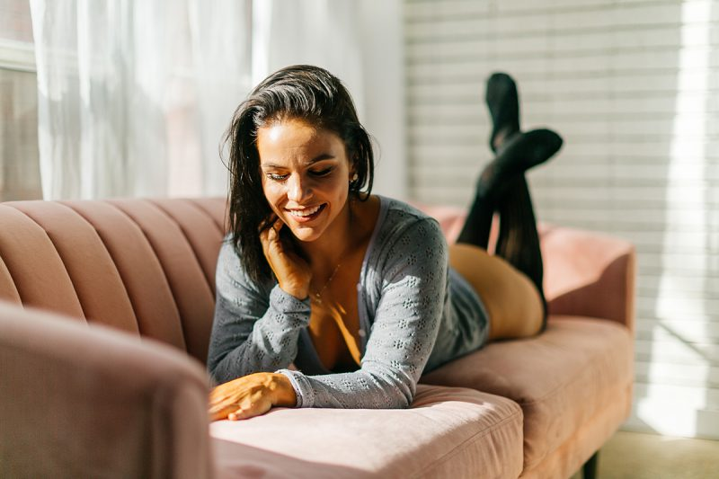 A beautiful young brunette woman poses on a pink couch in front of sheer curtains at a studio wearing a gray body suit and black leggings for a Denver Photo Collective boudoir photography session in Colorado