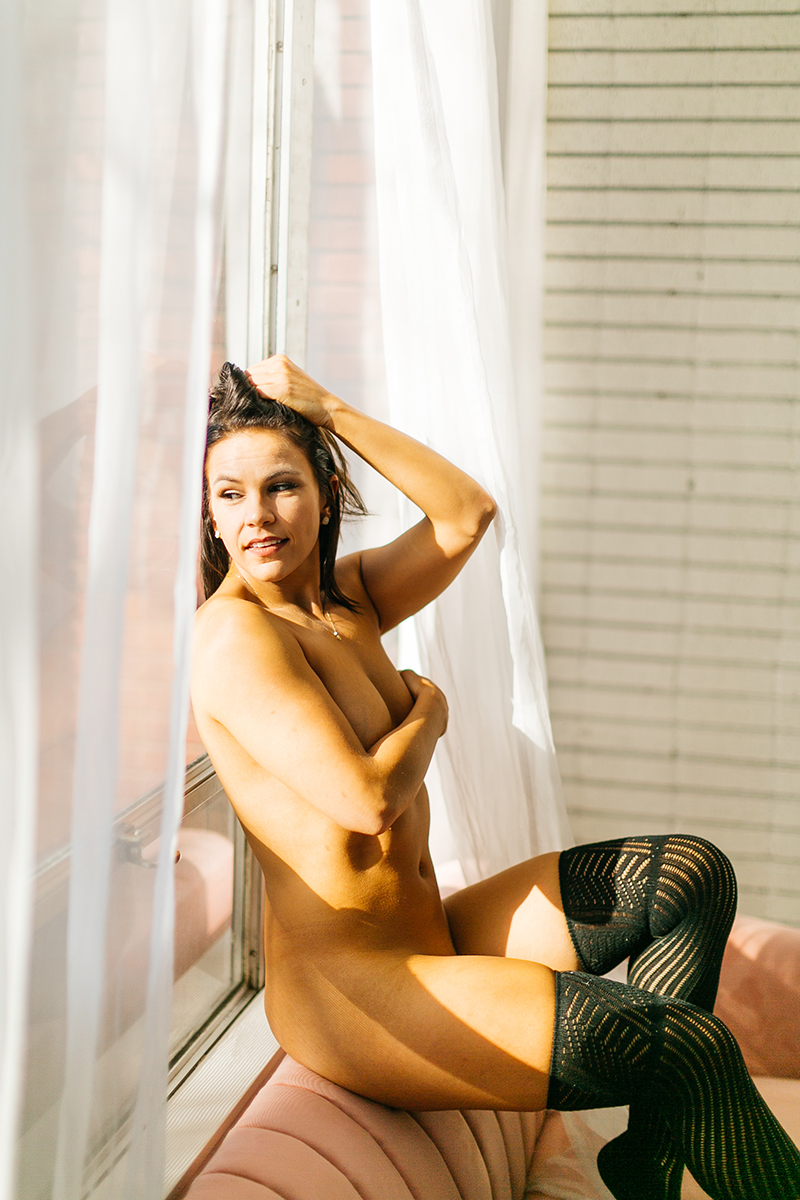 A beautiful young brunette woman poses nude on a pink couch in front of sheer curtains at a studio wearing black leggings for a Denver Photo Collective boudoir photography session in Colorado