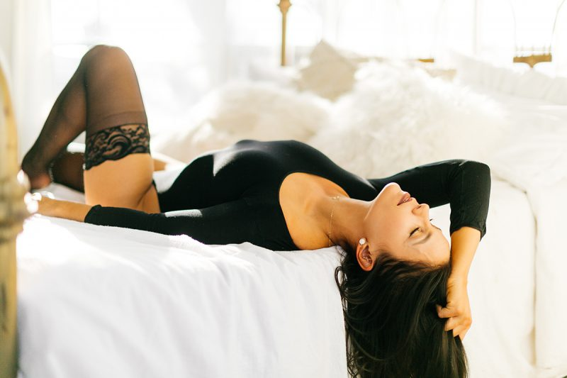 A beautiful young brunette woman poses on a white bed in front of sheer curtains at a studio wearing a black body suit and black leggings for a Denver Photo Collective boudoir photography session in Colorado