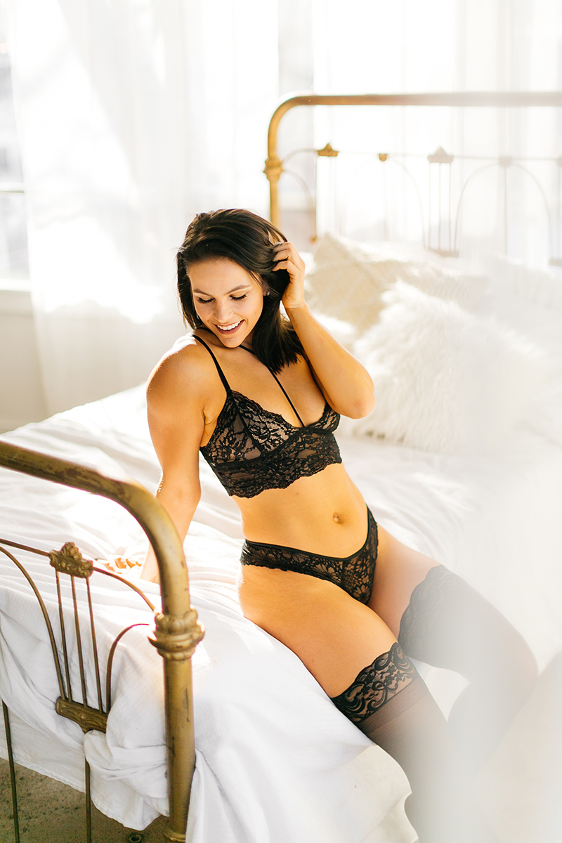 A beautiful young brunette woman poses on a white bed in front of sheer curtains at a studio wearing a lace black bra, black underwear and black leggings for a Denver Photo Collective boudoir photography session in Colorado
