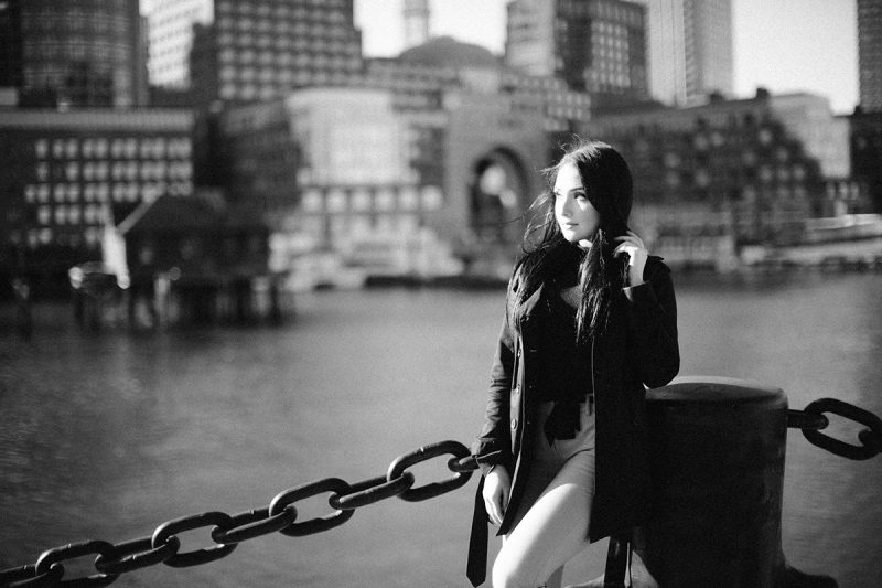 A beautiful young brunette poses for a Seaport fashion photography session wearing tan pants, a black shirt and a black jacket in front of the water with the city of Boston behind her
