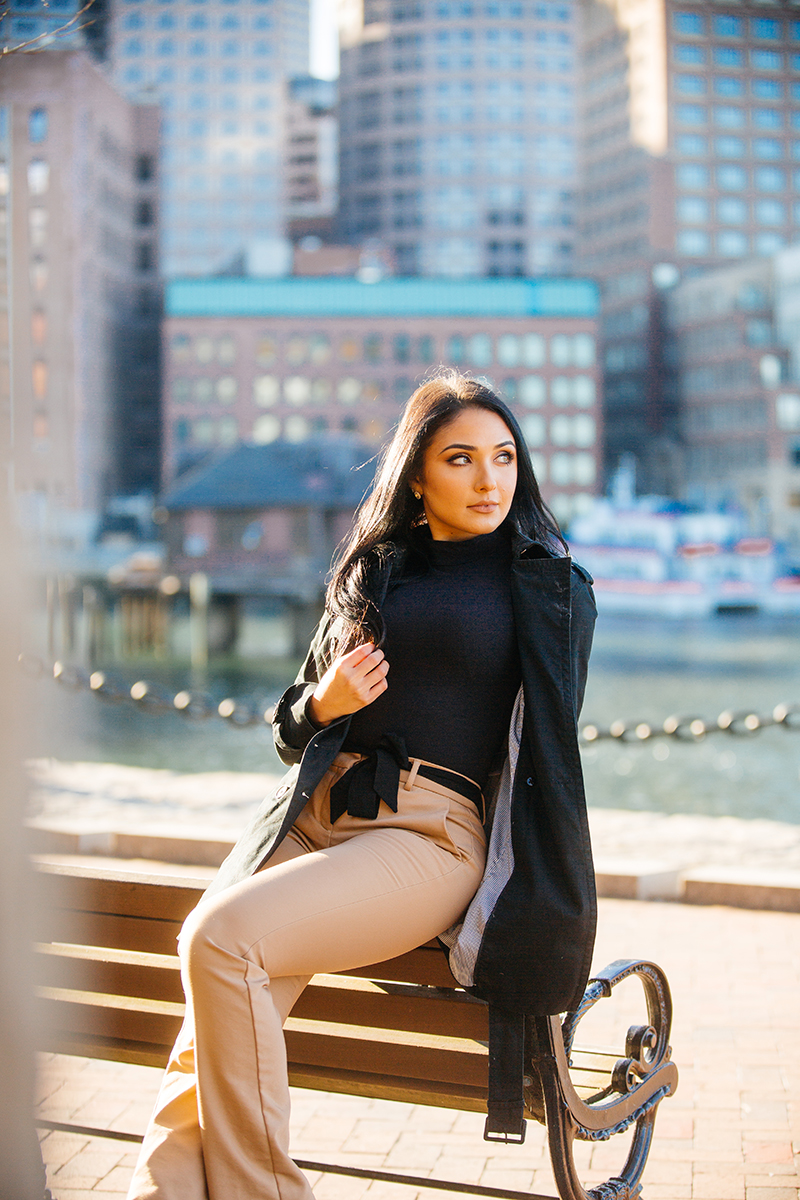 A beautiful young brunette poses for a Seaport fashion photography session wearing tan pants, a black shirt and a black jacket sitting on a bench in front of the water with the city of Boston behind her