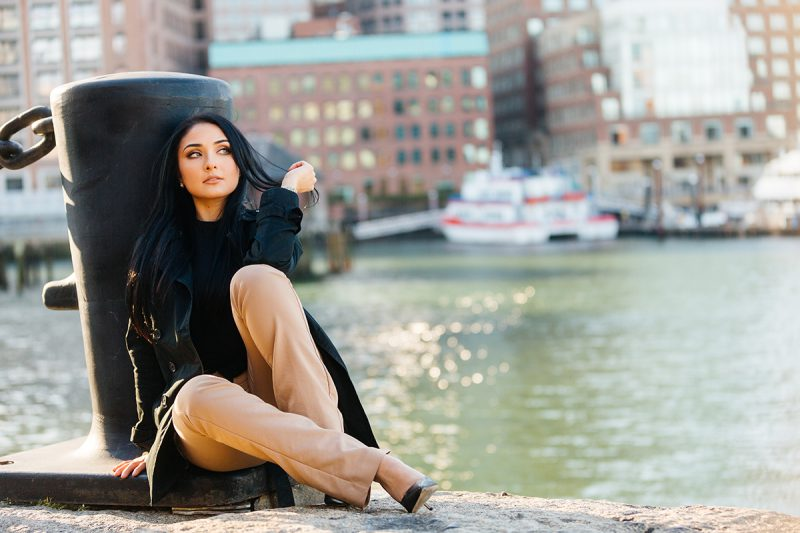 A beautiful young brunette poses for a Seaport fashion photography session wearing tan pants, a black shirt and a black jacket sitting on the path in front of the water with the city of Boston behind her