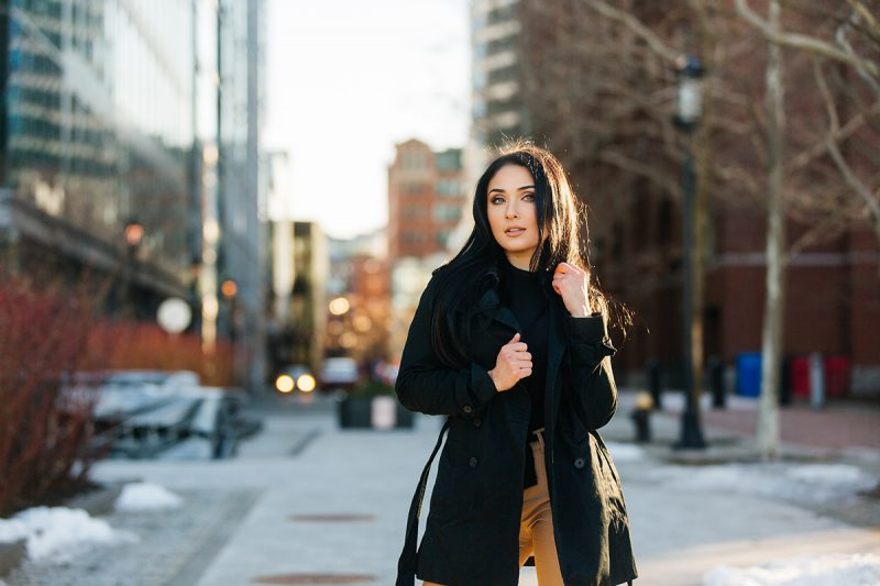 A beautiful young brunette poses for a Seaport fashion photography session wearing tan pants, a black shirt and a black jacket standing in the street with the city of Boston behind her