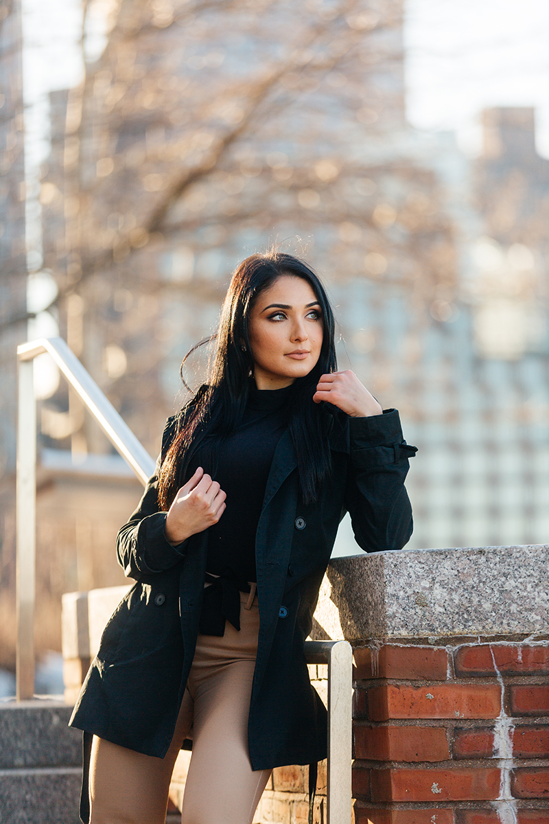 A beautiful young brunette poses for a Seaport fashion photography session wearing tan pants, a black shirt and a black on stairs leaning against a brick wall with the city of Boston behind her