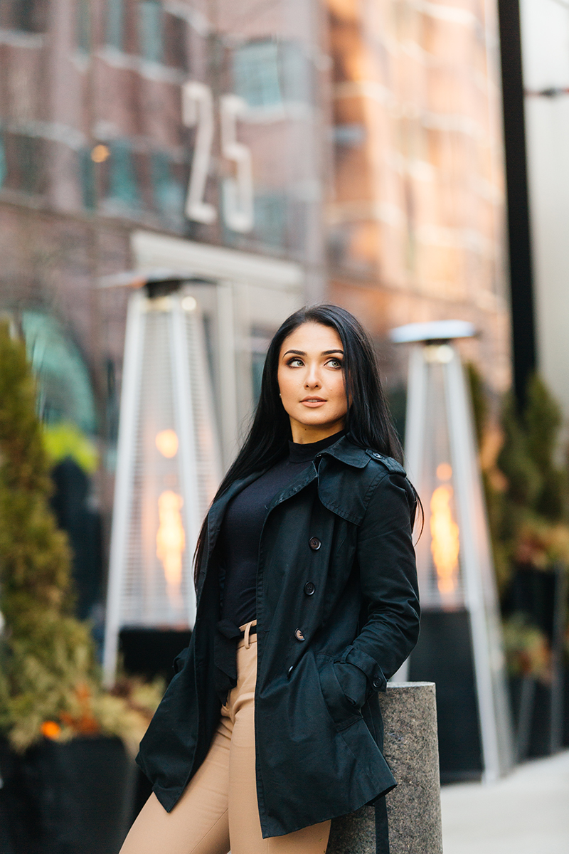 A beautiful young brunette poses for a Seaport fashion photography session wearing tan pants, a black shirt and a black leaning against a pillar with heating lamps in front of a building in Boston, Massachusetts