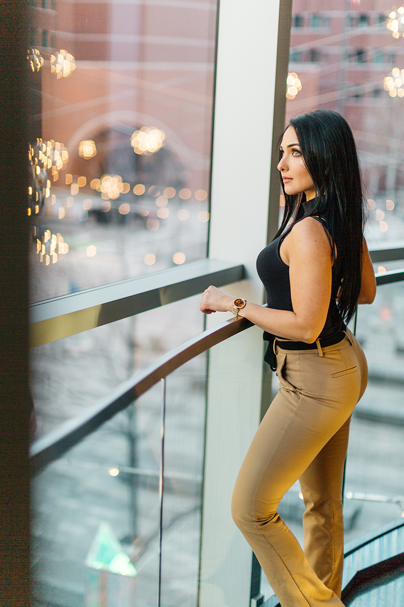 A beautiful young brunette poses for a Seaport fashion photography session wearing tan pants and a black shirt leaning against railing inside a building with the city of Boston outside in Massachusetts