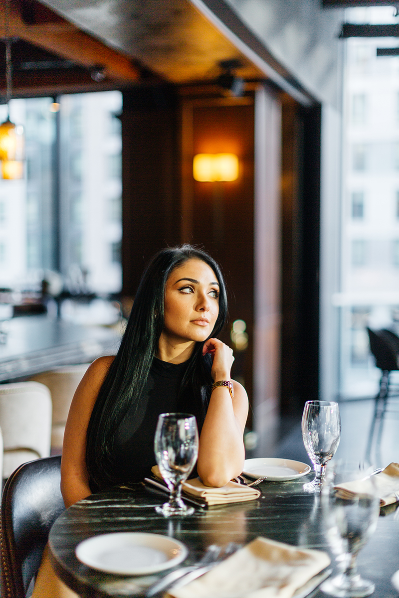 A beautiful young brunette poses for a Seaport fashion photography session wearing tan pants and a black shirt sitting at a table inside a building with the city of Boston outside in Massachusetts