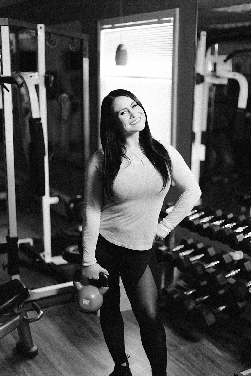 A beautiful brunette woman poses for a Sharon Massachusetts fitness photography session holding a kettle bell wearing a green workout shirt and black leggings in her gym near Boston, MA