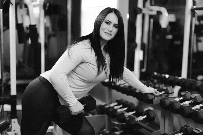 A beautiful brunette woman poses for a Sharon Massachusetts fitness photography session holding a dumbbell wearing a green workout shirt and black leggings in her gym near Boston, MA
