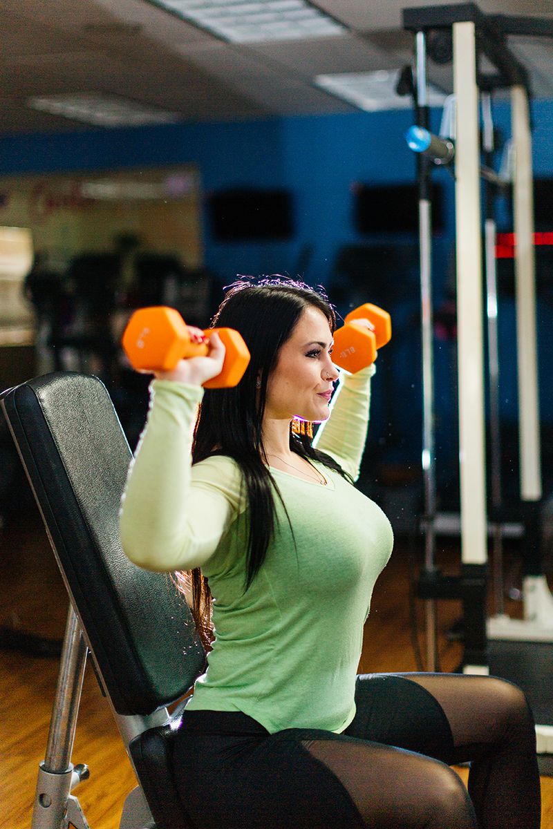 A beautiful brunette woman poses for a Sharon Massachusetts fitness photography session lifting dumbells wearing a green workout shirt and black leggings in her gym near Boston, MA