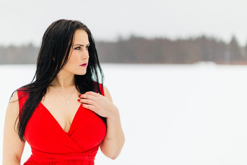 A beautiful brunette woman poses for a Sharon Massachusetts fitness photography session wearing a red dress in an open field covered in snow near Boston, MA