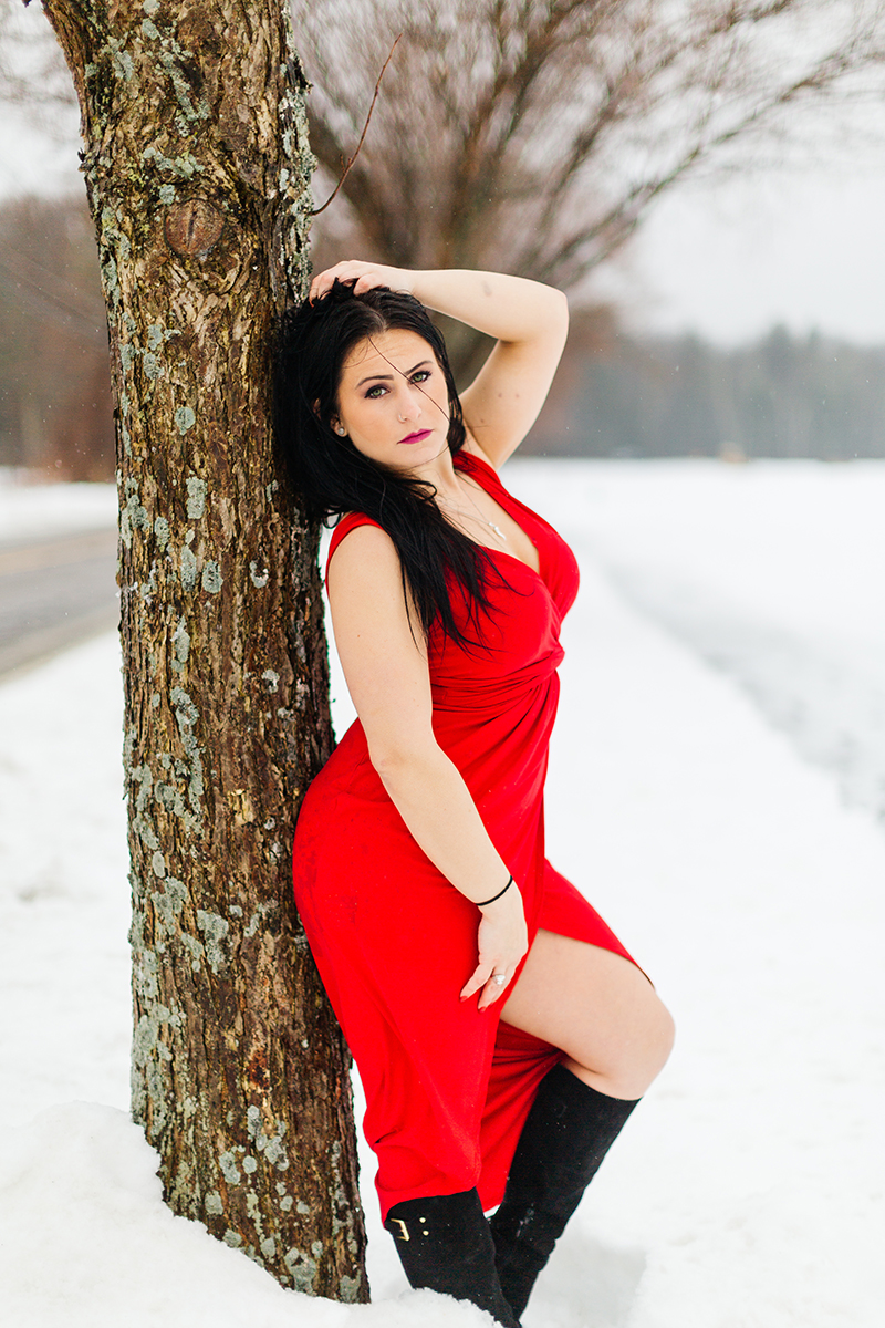 A beautiful brunette woman poses for a Sharon Massachusetts fitness photography session wearing a red dress leaning against a tree in an open field covered in snow near Boston, MA