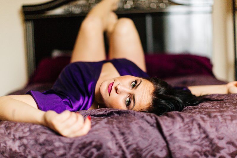 A beautiful brunette woman poses for a Sharon Massachusetts fitness photography session wearing a purple robe and a black bra and underwear set on her bed near Boston, MA