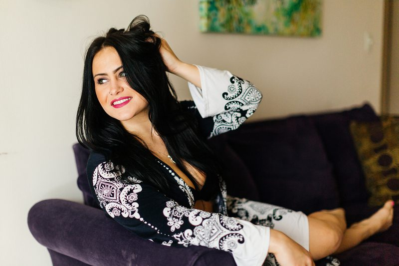 A beautiful brunette woman poses for a Sharon Massachusetts fitness photography session wearing a black and white robe with a black bra and underwear set on her couch near Boston, MA