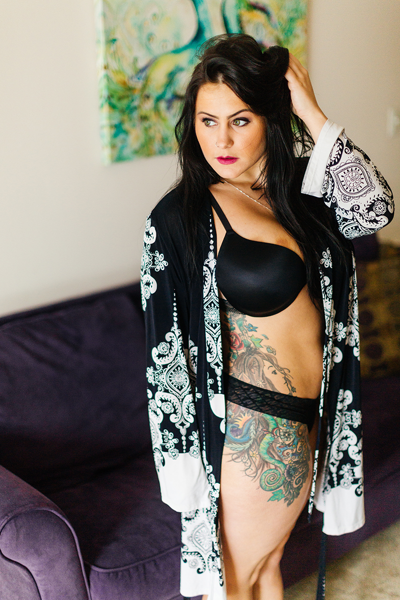 A beautiful brunette woman poses for a Sharon Massachusetts fitness photography session wearing a black and white robe with a black bra and underwear set in front of her couch near Boston, MA