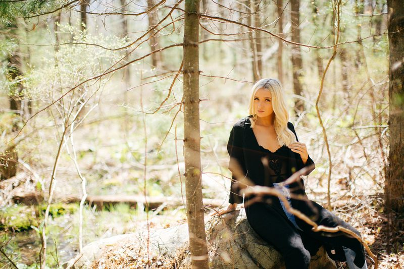 A beautiful young blonde woman poses for a Great Woods Conservation boudoir photography session wearing jeans, a black body suit and a black jacket while sitting on a log in the marshes near Mansfield, Massachusetts