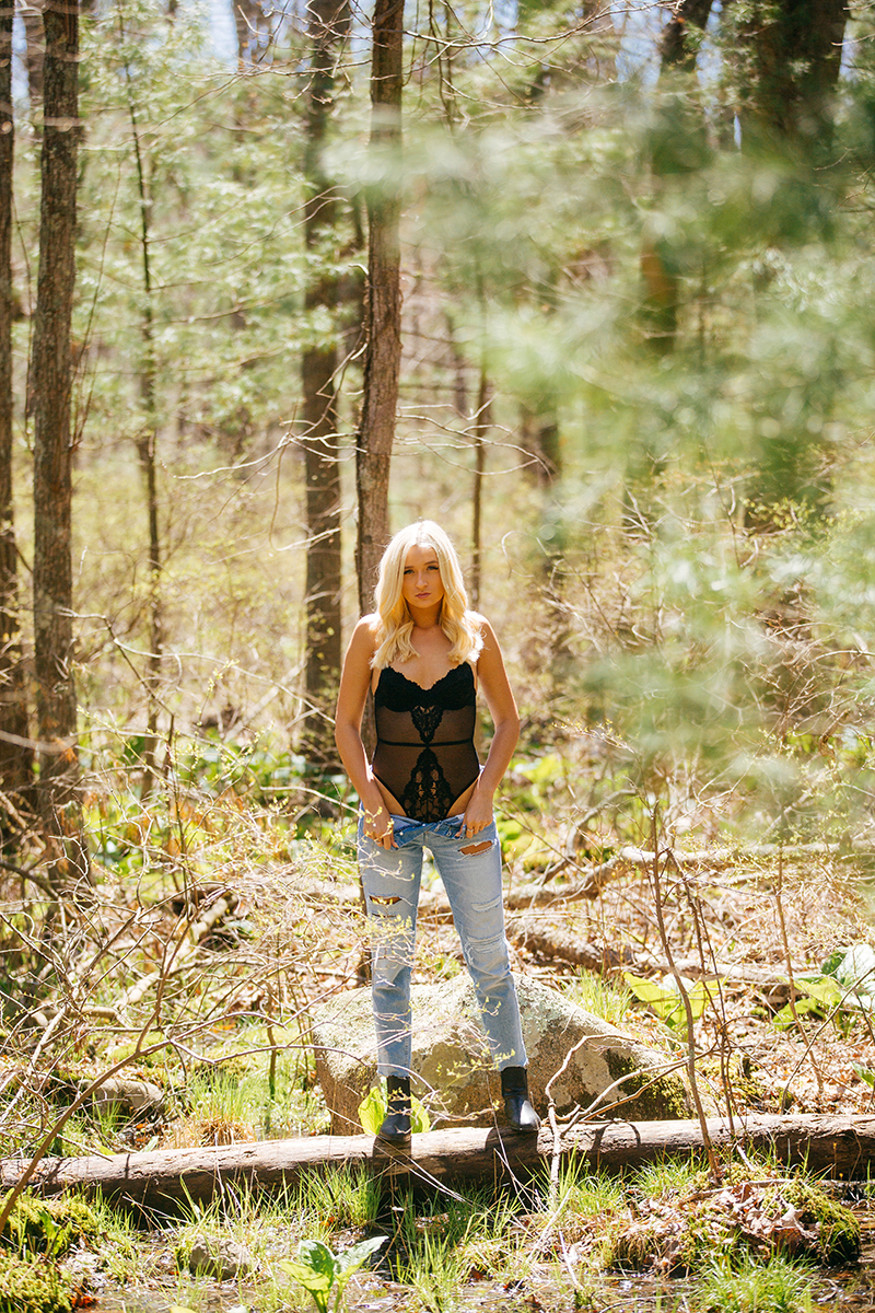 A beautiful young blonde woman poses for a Great Woods Conservation boudoir photography session wearing jeans and a black body suit standing in the marshes near Mansfield, Massachusetts