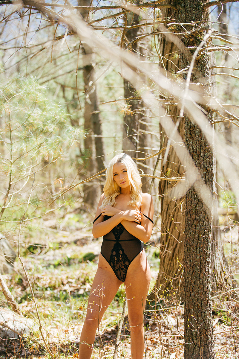 A beautiful young blonde woman poses for a Great Woods Conservation boudoir photography session wearing a black body suit standing in trees in marshes near Mansfield, Massachusetts