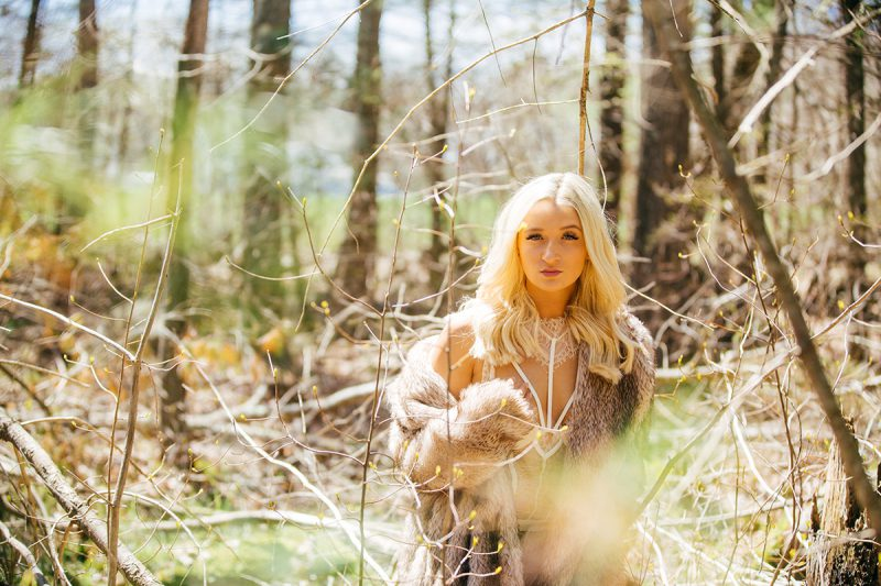 A beautiful young blonde woman poses for a Great Woods Conservation boudoir photography session wearing white lingerie and a fur coat standing in trees in marshes near Mansfield, Massachusetts