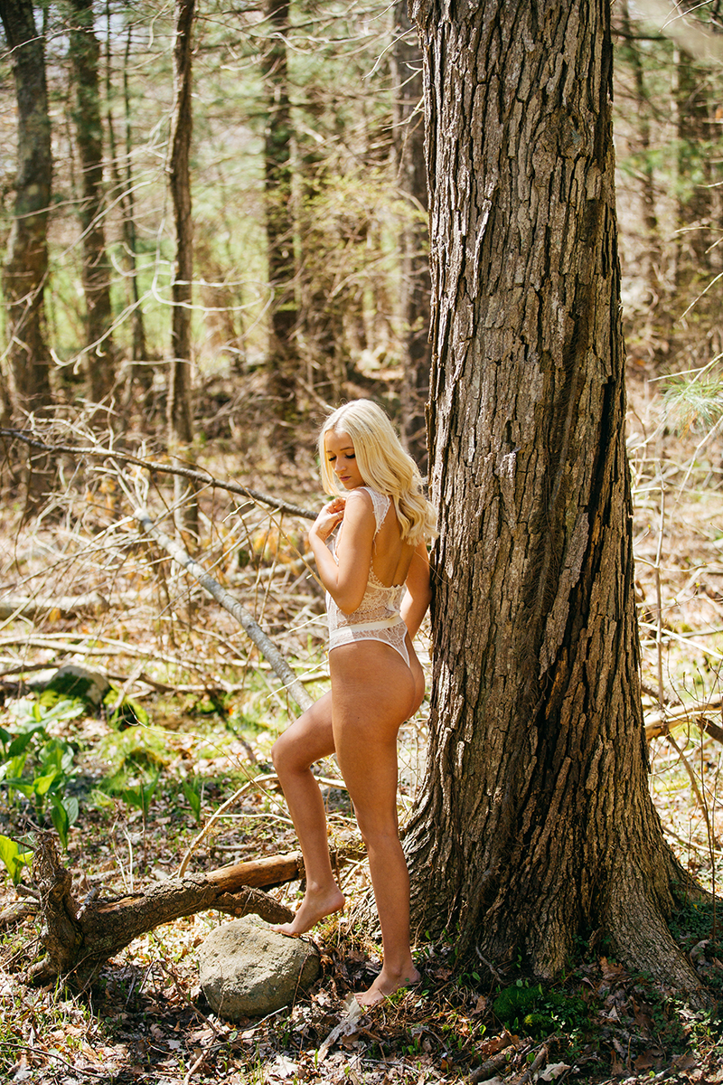 A beautiful young blonde woman poses for a Great Woods Conservation boudoir photography session wearing white lingerie leaning on a tree in marshes near Mansfield, Massachusetts