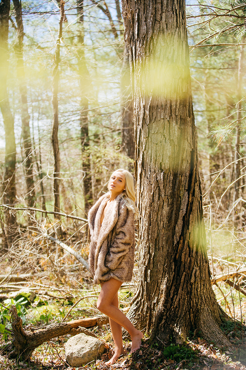 A beautiful young blonde woman poses naked for a Great Woods Conservation boudoir photography session wearing a fur coat leaning on a tree in marshes near Mansfield, Massachusetts