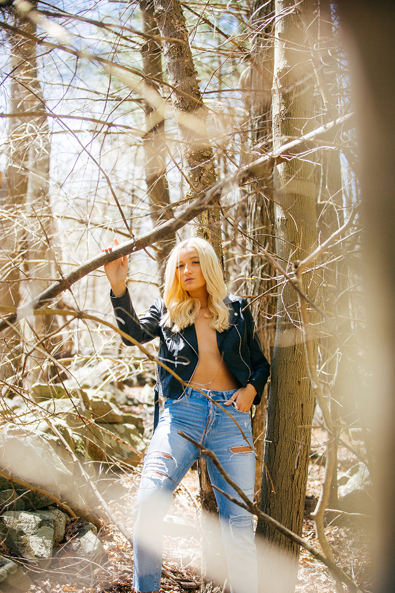 A beautiful young blonde woman poses topless for a Great Woods Conservation boudoir photography session wearing jeans and a black leather jacket leaning on a tree in marshes near Mansfield, Massachusetts