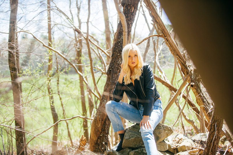 A beautiful young blonde woman poses topless for a Great Woods Conservation boudoir photography session wearing jeans and a black leather jacket surrounded by trees in marshes near Mansfield, Massachusetts