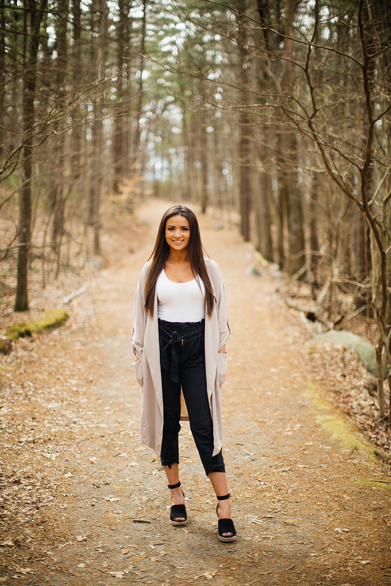 A beautiful young brunette poses for a Blue Hills Reservation boudoir photography session wearing black pants, a white shirt and a pink shawl on a path in the woods near Milton, Massachusetts