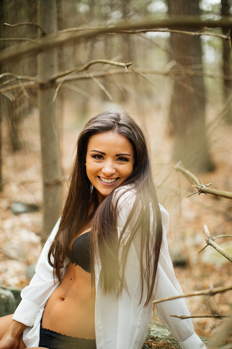 A beautiful young brunette poses for a Blue Hills Reservation boudoir photography session wearing a black bra and underwear set with a white button up shirt sitting on a log in the woods near Milton, Massachusetts