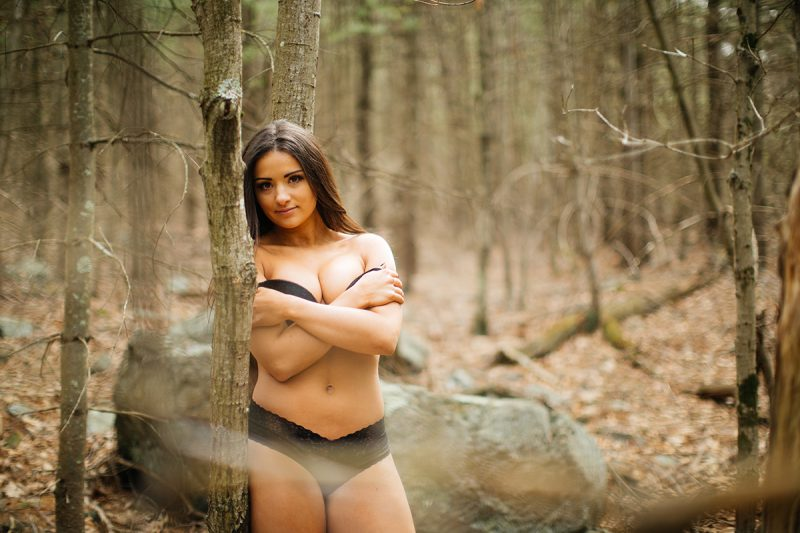A beautiful young brunette poses for a Blue Hills Reservation boudoir photography session wearing a black bra and underwear set leaning on a tree in the woods near Milton, Massachusetts