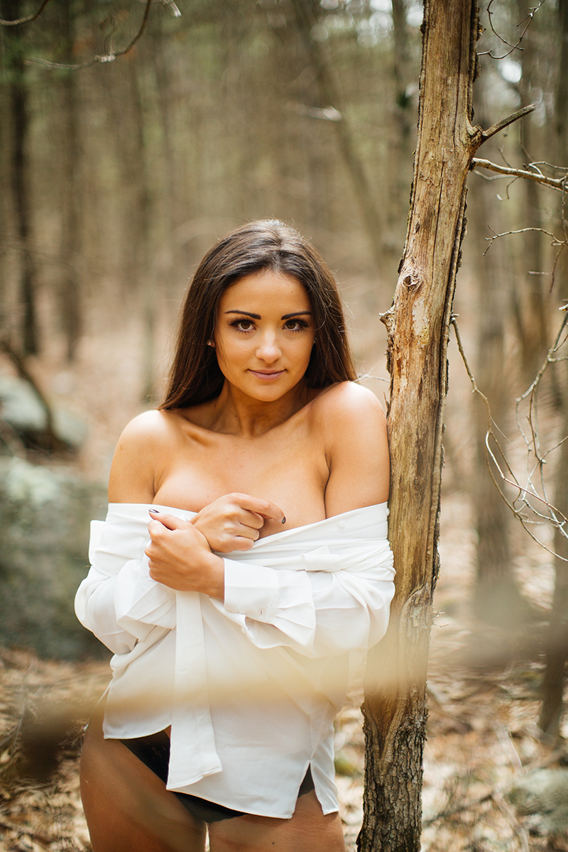 A beautiful young brunette poses topless for a Blue Hills Reservation boudoir photography session wearing black underwear and a white button up shirt leaning on a tree in the woods near Milton, Massachusetts