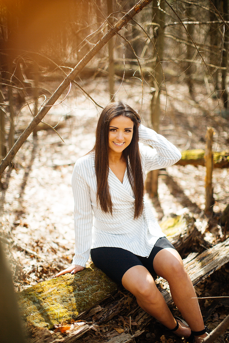 A beautiful young brunette poses for a Blue Hills Reservation boudoir photography session wearing a striped white button up shirt and black shorts sitting on a log near a pond in the woods near Milton, Massachusetts